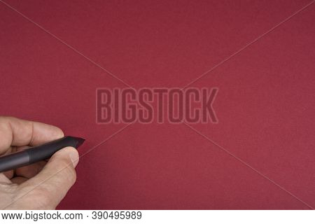 Hand And Pen On A Blank Red Background