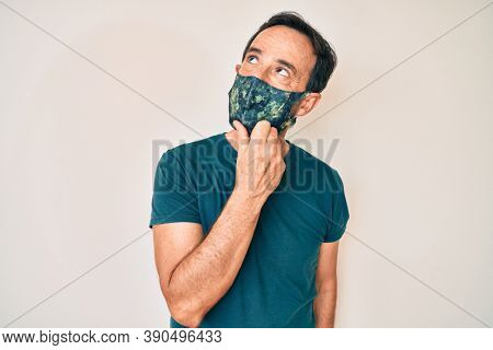 Middle age hispanic man wearing covid-19 protection mask serious face thinking about question with hand on chin, thoughtful about confusing idea