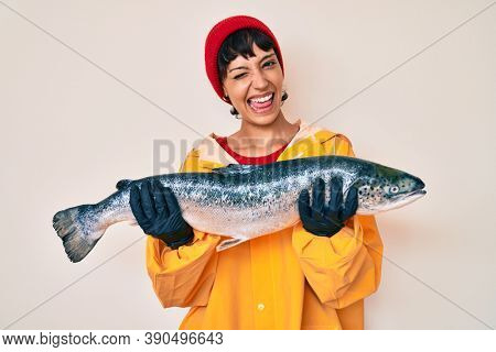 Beautiful brunettte fisher woman wearing raincoat holding fresh salmon winking looking at the camera with sexy expression, cheerful and happy face.
