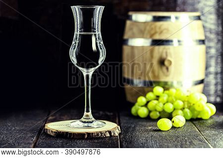 Glass Of Grappa On Wooden Background With Old Oak Barrel, Grape-based Drink, Distilled. Selective Fo