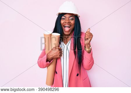 Young african american woman wearing architect hardhat holding blueprints screaming proud, celebrating victory and success very excited with raised arms