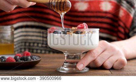 Yogurt Cream Dessert With Berries, Granola And Honey. Woman Pouring Honey Into Greek Yogurt