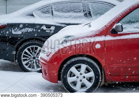 Snowfall. Two Black And Red Snow-covered Cars Are Parked In The Winter Parking Lot.