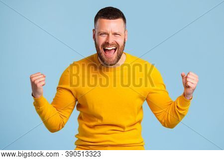 Happy Expressive Man In  Yellow Sweater Shouts Celebrating Victory Success And Triumph On A Blue Bac