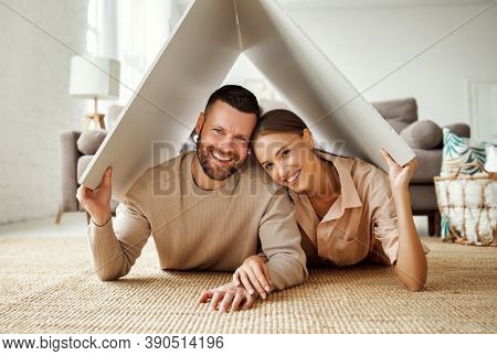 Concept Housing A Young Family Couple. Man And Woman  Under Fake Roof In A New Home During Relocatio