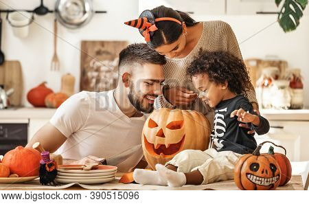 Cheerful Multi Ethnic Family Parents With Son Smiling  While Creating Jack O Lantern From Pumpkin Du