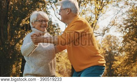 Happy Old Couple Dancing In Park. Senior Man Flirting With Elderly Woman. Romance At Old Age Autumn