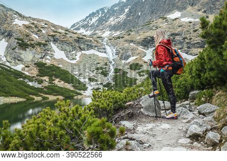 Woman hiker, hiking backpacker traveler camper walking on the top of mountain in sunny day under sun light. Beautiful mountain landscape view.