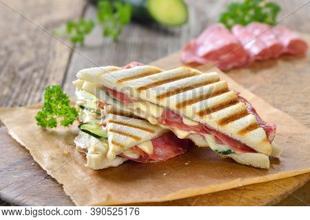 Pressed And Toasted Double Panini With Italian Salami And Cheese Served On Sandwich Paper On A Woode