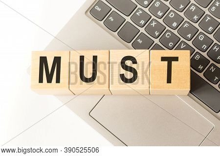 Word Must. Wooden Small Cubes With Letters Isolated On White Background With Copy Space Available. B