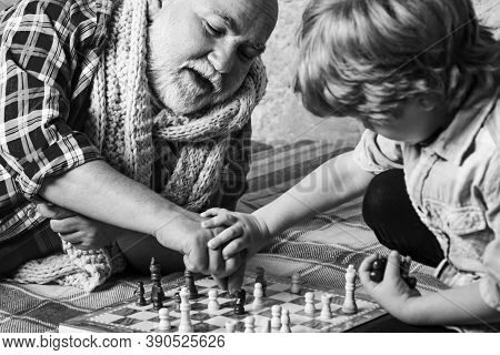 Handsome Grandpa And Grandson Are Playing Chess While Spending Time Together At Home. Chess Hobbies