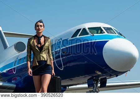 Stewardess In Blue Uniform. Traveling And Jet Plane Flying Concept. Beautiful Charming Stewardess Dr