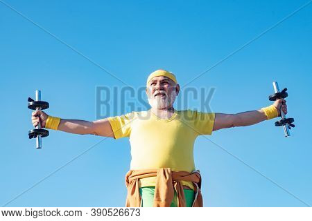 Senior Man In Health Club. Senior Fitness Man Training With Dumbbells Isolated On Blue Background. S