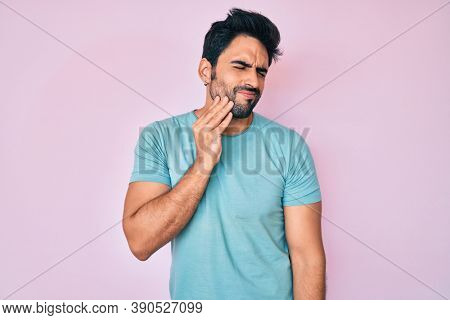 Handsome hispanic man with beard wearing casual clothes touching mouth with hand with painful expression because of toothache or dental illness on teeth. dentist