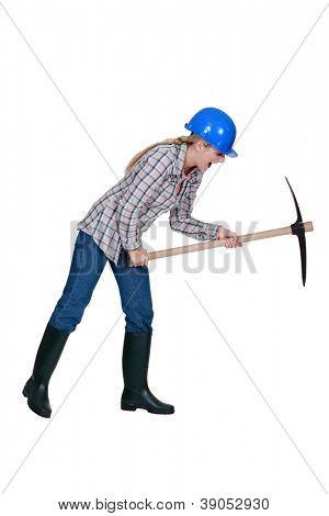 Tradeswoman using a pickaxe