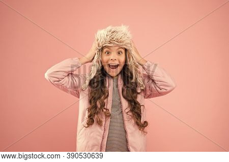 Playful Kid Girl Wear Fur Hat With Ear Flaps Pink Background. Soft Furry Accessory. Child Long Hair