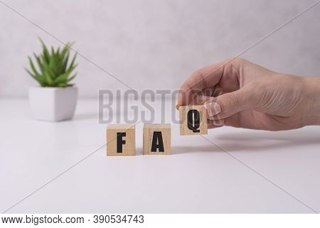 Businessman Puts Wooden Blocks With The Word Faq Frequently Asked Questions . Collection Of Frequent