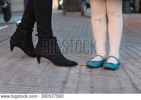 Human Feet Of A Woman And A Girl In The Street, Black Boots And Mary Janes Shoes