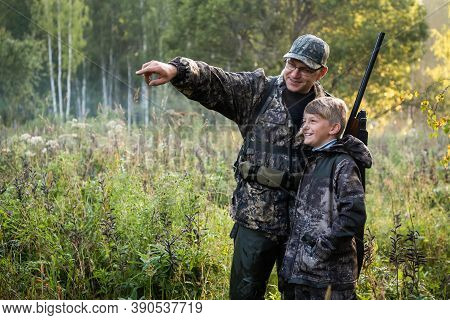 A Young Boy On The Hunt With An Experienced Instructor In The Forest. Autumn. Hunting For Upland Wil