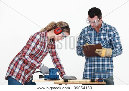 Man evaluating a tradeswoman on her use of a jigsaw