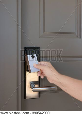 Hand Holding Keycard To Scan Electronic Lock Door In Order To Open The Door