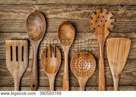 wooden kitchen cooking utensils set on a rustic weathered barn wood background