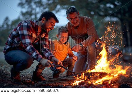 Father, son and grandson lit up a campfire in the forest on a beautiful autumn dusk