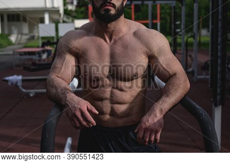 Active Healthy Lifestyle Of Strong Male Athlete With Beard And Mighty Physique On Sport Outdoor Grou