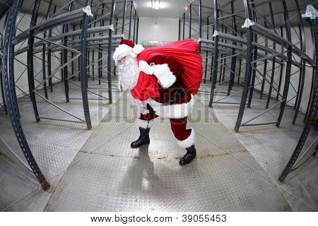 Santa Claus with red sack in empty storehouse - fish eye photo