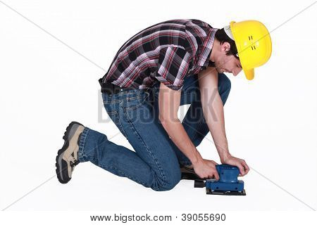 Workman using an electric sander