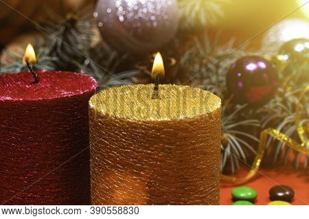 A Beautiful Christmas Image - A Burning Candle In Gold Color Against The Background Of The Christmas
