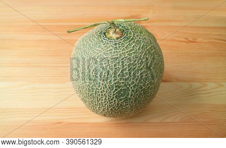 Fresh Ripe Muskmelon Or Cantaloupe Melon Fruit With Stem Isolated On Wooden Table