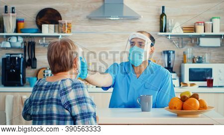 Doctor With Face Mask Checking Senior Woman Temperature Using Gun Thermometer During Home Visit. Soc