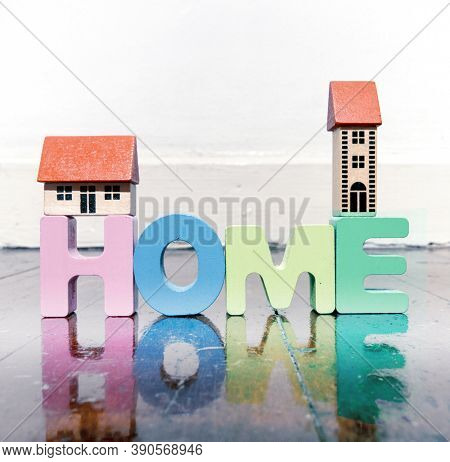 the word home with wooden letters on a wooden floor with reflection