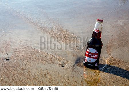 Old Orchard Beach, USA - 3rd September 2014: Glass bottle of the iconic soft drink Dr Pepper, being kept cold in the sea at Old Orchard Beach, USA.