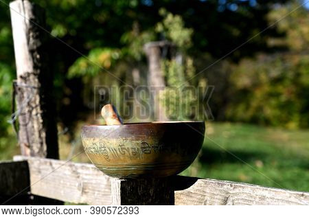 Tibetan Singing Bowl On A Wooden Fence. Translation Of Mantras. Transform Your Impure Body, Speech A