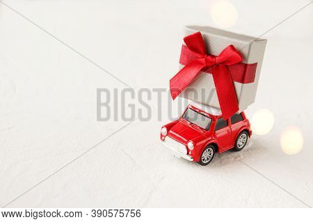 Red Toy Car Delivering Christmas Or New Year Gifts On White Background. Christmas Greeting Card Conc