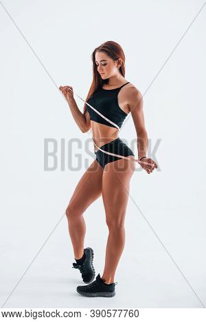 Holds Measuring Tape. Young Woman With Slim Body Type Isolated Against White Background.