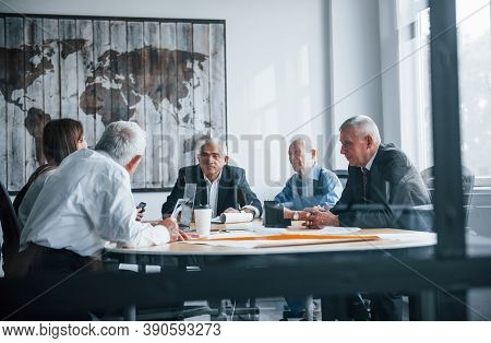 Aged Team Of Elderly Businessman Architects Have A Meeting In The Office And Works With Young Woman.