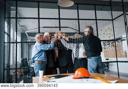 Job Well Done, Gives High Five To Each Other. Aged Team Of Elderly Businessman Architects Stands In