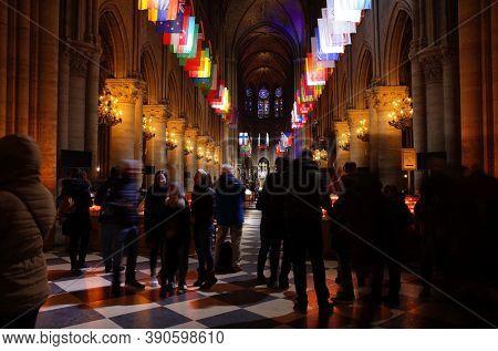Paris, France - November 20, 2018: Crowd of tourists inside cathedral Notre Dame de Paris. Long exposure photo with blurry people