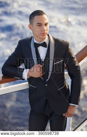 Portrait Of Handsome Young Elegant Man Standing On Ship Deck In Formal Tuxedo. Luxury Cruise Ship Su