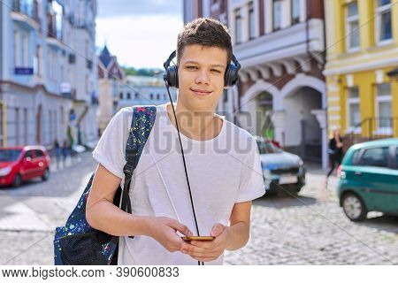 Portrait Of Student Boy Teenager With Headphones Smartphone Backpack Looking At Camera, City Street
