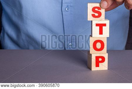 A Man In A Blue Shirt Composes The Word Stop From Wooden Cubes Vertically
