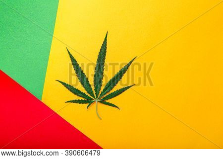 Weed Ganja Green Hemp Leaf On Rastaman Flag, Red Green Yellow Background. Cannabis Leaf. Weed Legali
