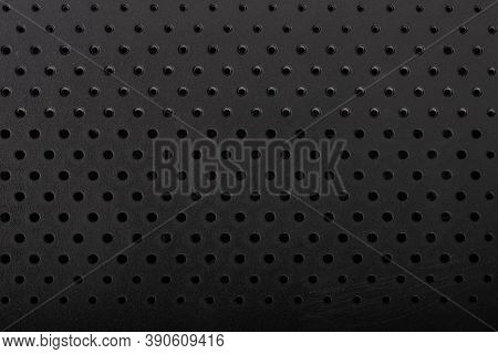 Black perforated plastic texture, surface with dots