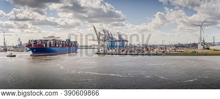Panorama Of A Container Terminal With Arriving Container Ship And Tug In Hamburg