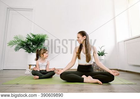 Pretty Caucasian Mom With Cute Kid Daughter Doing Yoga Exercise At Home Or Studio, Sitting In Lotus