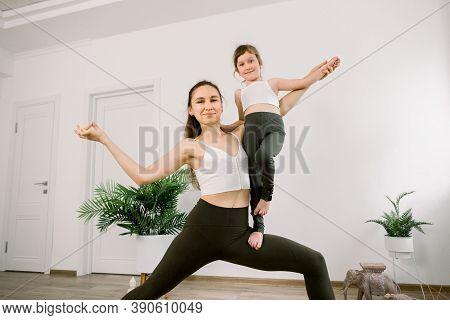Vitality And Yoga Lifestyle Concept. Slim Sportive Mom And Cute Cheerful Joyful Girl, Wearing Simila