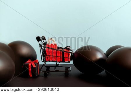 Red And Black Gift Boxes In Shopping Cart On Blue Background With Baubles, Copy Space. Black Friday
